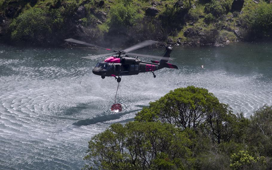 An Army National Guard UH-60 Black Hawk helicopter picks up water from Pardee Reservoir, in Ione, California, Saturday, April 14, 2018, during interagency aircrew training with CAL FIRE.