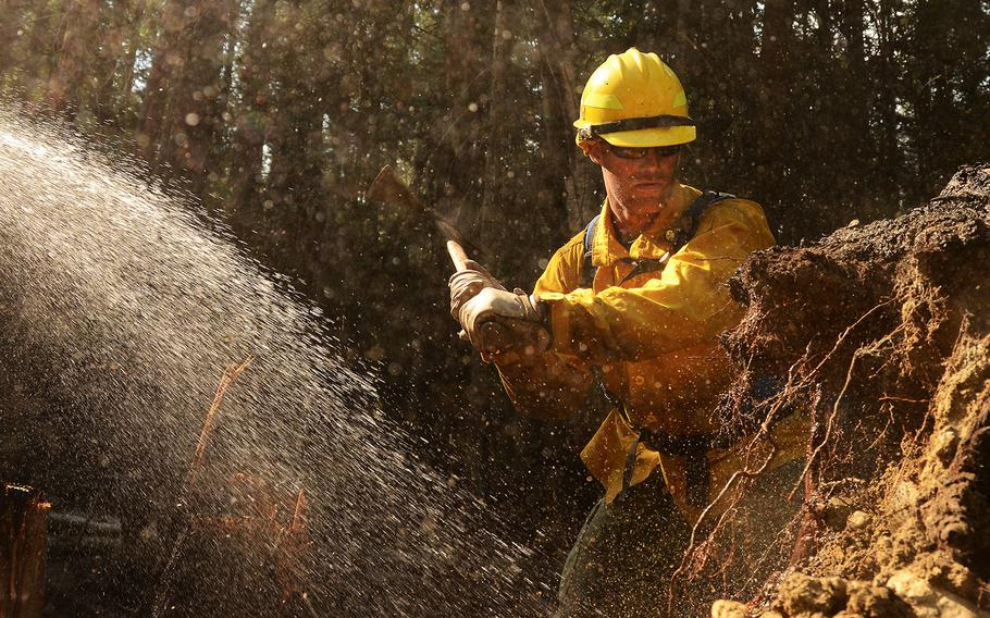 Washington Air National Guard Master Sgt. Luke Anderson, 141st Communications Squadron mops up an area of the Sheep Creek fire Aug. 6, 2018, near Northport, Wash.