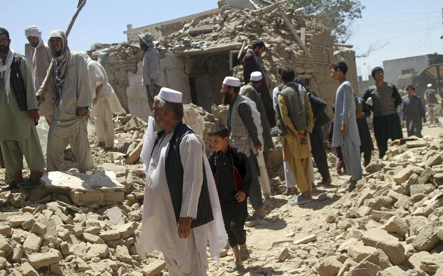 Afghan men stand near a damaged house following a Taliban attack in Ghazni, Afghanistan, Wednesday, Aug. 15, 2018. A Taliban assault on two adjacent checkpoints in northern Afghanistan killed at least 30 soldiers and police, officials said Wednesday.