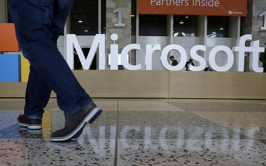 In this April 28, 2015, file photo, a man walks past a Microsoft sign set up for the Microsoft BUILD conference at Moscone Center in San Francisco. Microsoft has uncovered new hacking attempts by Russia targeting U.S. political groups ahead of the midterm elections. The company said Tuesday, Aug. 21, 2018, that a group tied to the Russian government created fake websites that appeared to spoof two American conservative organizations: the Hudson Institute and the International Republican Institute.