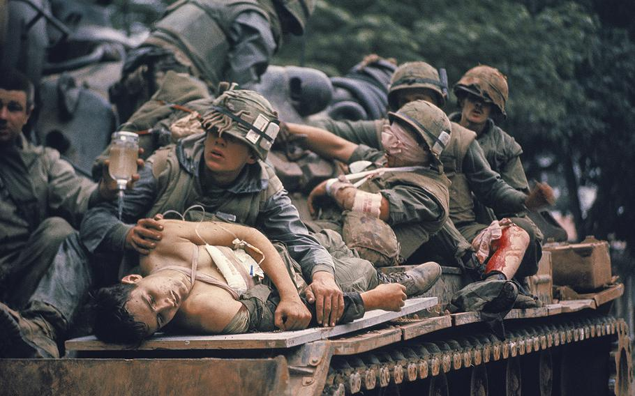 A.B. Grantham, foreground, and other wounded U.S. Marines are evacuated on a tank at Hue, South Vietnam, during the Tet offensive in February, 1968.