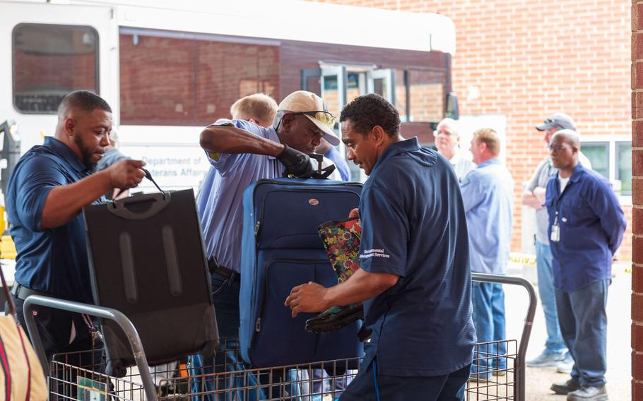 Workers help unload luggage for patients evacuated from Hampton VA Medical Center to Richmond VA Medical Center in Virginia on Wednesday, Sept. 12, 2018.