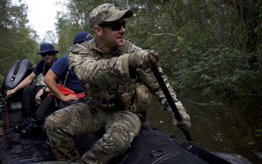 A member of Coast Guard Tactical Law Enforcement Team South rows a shallow-water craft through debris filled water while conducting Hurricane Florence search and rescue operations in Brunswick County, North Carolina, Sept. 17, 2018.