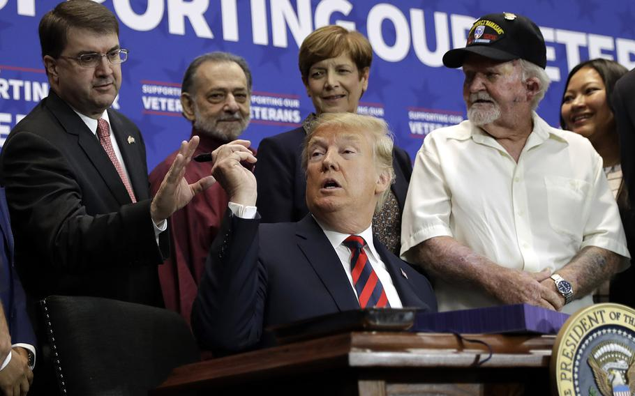 President Donald Trump hands a pen to Veterans Affairs Secretary Robert Wilkie during a spending bill signing ceremony at VA Southern Nevada Healthcare System, Friday, Sept. 21, 2018, in Las Vegas.