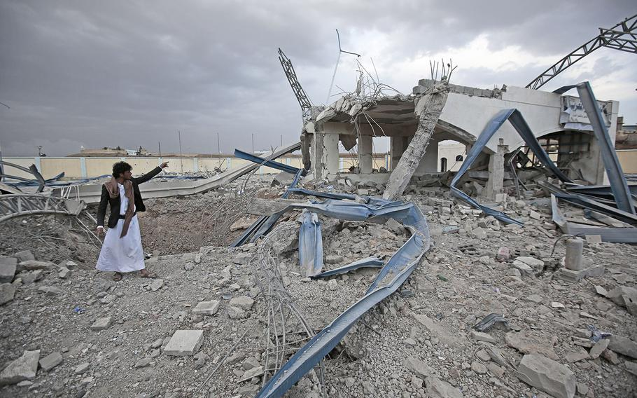 A Yemeni man inspects a destroyed petrol station after it was targeted by Saudi-led airstrikes on the outskirts of Sanaa in May 2018.