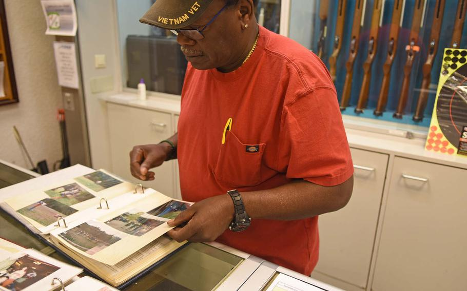 Calvin Churchill, a long-time Kaiserslautern Rod and Gun Club employee, pages through scrapbooks containing keepsakes from the club's storied history.