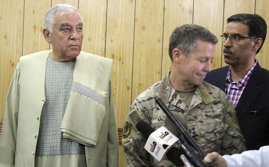Kandahar Gov. Zalmay Wesa, left, stands with the head of NATO troops in Afghanistan, Gen. Scott Miller, center, and a translator, during a meeting, in Kandahar, Afghanistan, Thursday, Oct. 18, 2018. Wesa was among three top officials in Afghanistan's Kandahar province who were killed when their own guards opened fire on them at the security conference, the deputy provincial governor said. A Taliban spokesman said the target was Miller, who escaped without injury, according to NATO.