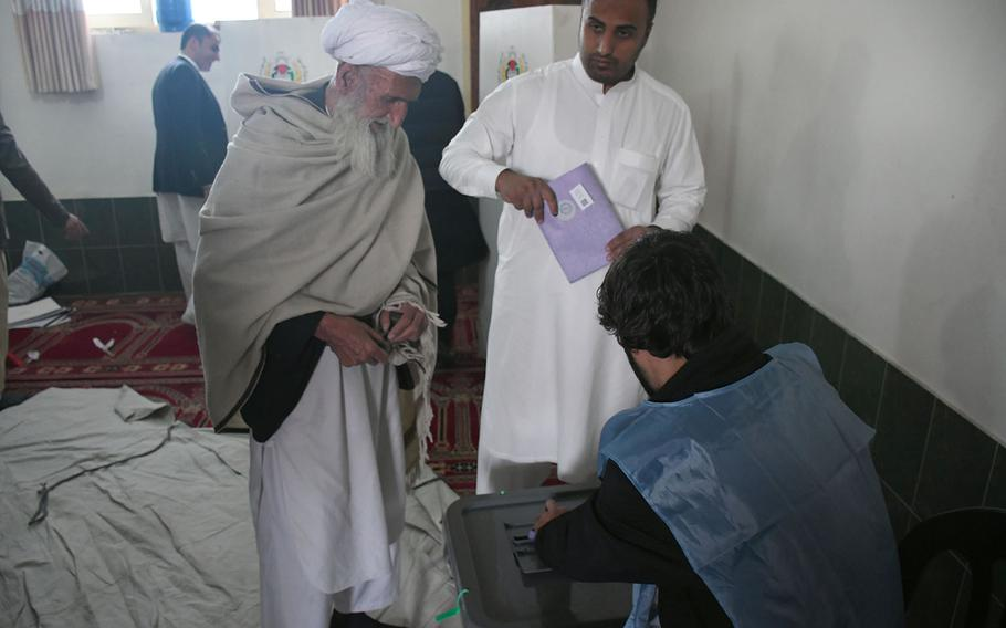 An election official helps a man cast his ballot for Afghanistan's parliamentary elections on Sunday, Oct. 21, 2018. Voting at the polling station was extended for a second day because of various complications.
