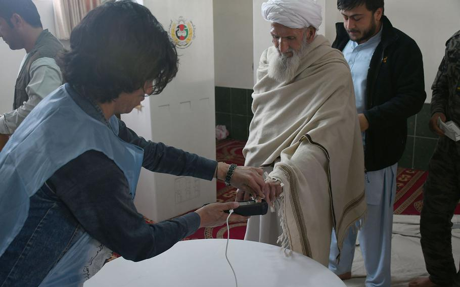 A man places his finger on a biometric machine at a voting center in Kabul before casting his ballot in the country's parliamentary elections on Sunday, Oct. 21, 2018. Voting at the center was extended from Election Day on Saturday, partly because of problems with the machines.