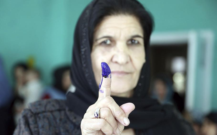 An Afghan woman shows her inked finger after casting her vote at a polling station during the Parliamentary elections in Kabul, Afghanistan, Saturday, Oct. 20, 2018.
