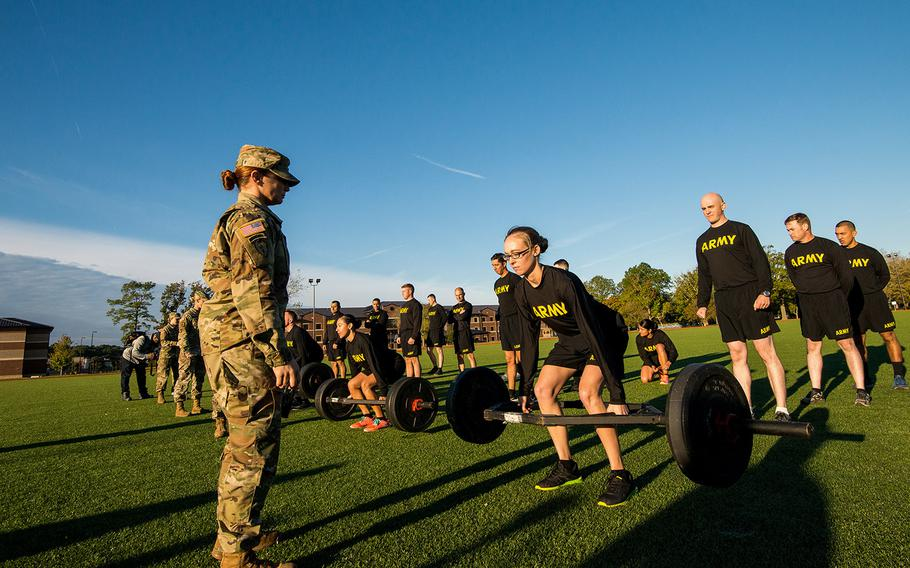 Army Staff Sgt. Jessica Smiley, a test grader with the Army's Center for Initial Military Training, looks on as soldiers with the 128th Aviation Brigade at Fort Eustis, Va., demonstrate the deadlift, the first of six events of the new Army Combat Fitness Test on Oct. 23, 2018.