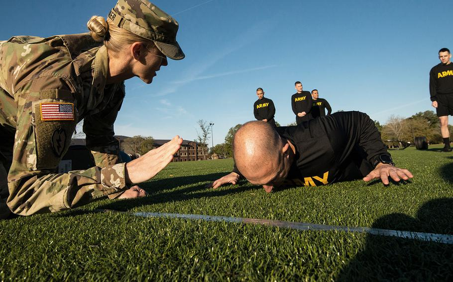 Army Master Sgt. Shelley Horner grades a 128th Aviation Brigade attempting the hand release pushup portion of the Army's new Army Combat Fitness Test during a demonstration of the new test on Tuesday, Oct. 23, 2018 at Fort Eustis, Va.