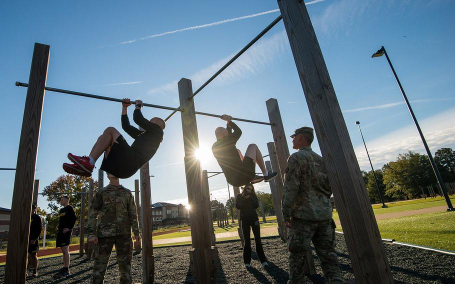Soldiers assigned to the 128th Aviation Brigade at Fort Eustis, Va., attempt the leg tuck portion of the Army's new Army Combat Fitness Test during a demonstration Tuesday, Oct. 23, 2018 at the installation. The six-event test is undergoing testing and is scheduled to be fully implemented across the service by October of 2020.