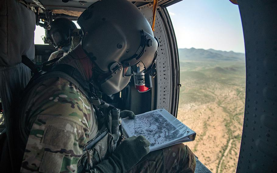 A National Guard crew member consults a map while enroute to a call for assistance by Border Patrol agents on the ground. The UH-60 Blackhawk helicopter crew participated in Tucson Sector's Mobile Response Team Monday, Aug. 13, 2018.