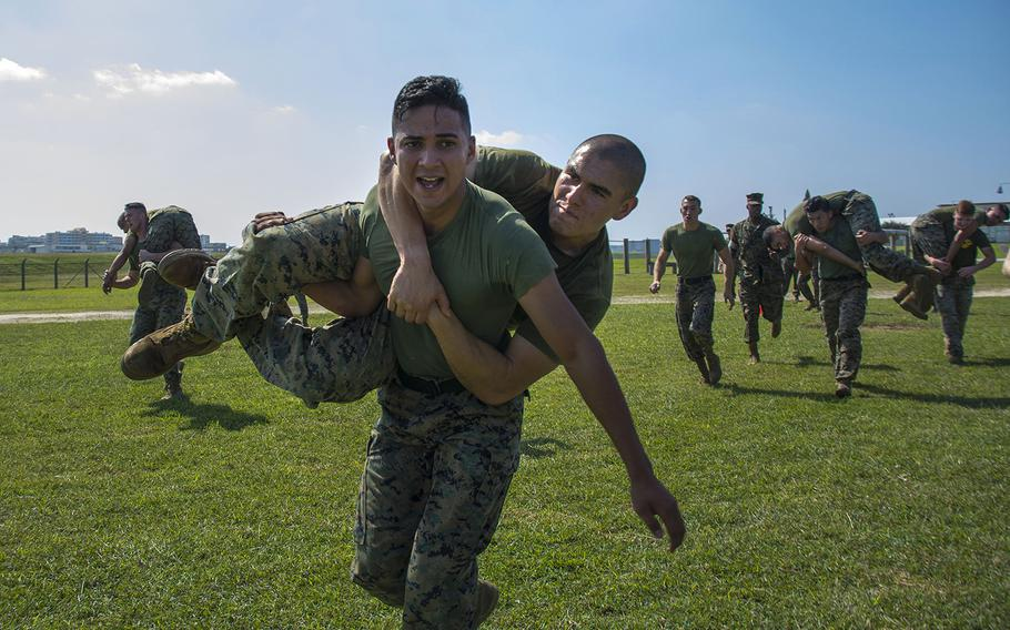 Marines perform fireman carries during a Warrior Games event at Marine Corps Air Station Futenma, Okinawa, Oct. 25, 2018.