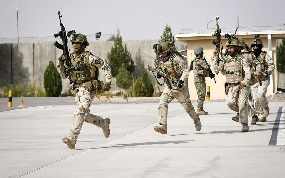 A sergeant in an elite Afghan police special forces unit in Herat leads the charge toward waiting Humvees during a prep drill for a raid to nab a Taliban leader Oct. 28, 2018.
