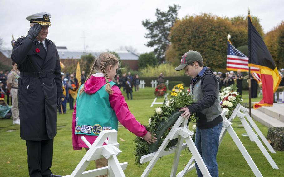 Adm. James Foggo, the Navy's top Europe and Africa commander, salutes a wreath being placed by American children at Flanders Field American Cemetery and Memorial on Nov. 11, 2018.