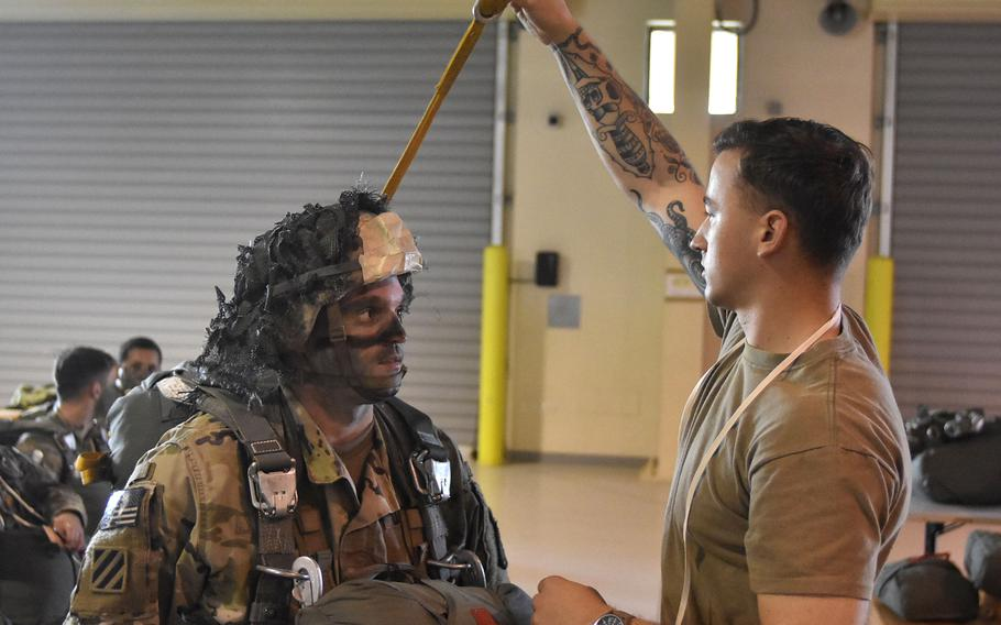 Staff Sgt. Nate De Pretis inspects the gear of Staff Sgt. Gordon Black on Wednesday, Nov. 14, 2018, in preparation for a jump into France for operation Falcon Amarante.