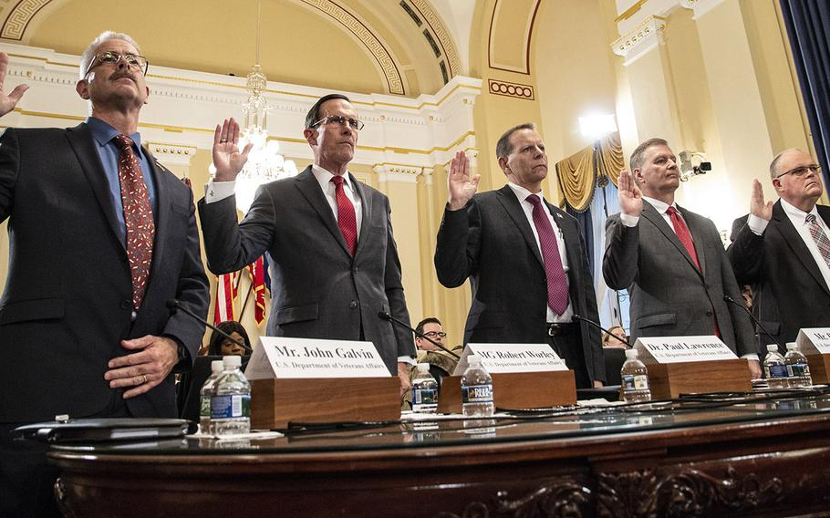 Witnesses are sworn in at the start of a House Veterans' Affairs subcommittee hearing on delays in GI Bill payments, Nov. 15, 2018 on Capitol Hill. From left to right are Mr. John J. Galvin, associate deputy assistant secretary for information technology operations and services in the VA's Office of Information and Technology; retired Air Force Maj. Gen. Robert M. Worley II, director of education service for the Veterans Benefit Administration; Paul R. Lawrence, the VBA's undersecretary for benefits; Bill James. deputy assistant secretary for development and operations in the VA's Office of Information & Technology; and Richard Crowe, senior vice president at Booz Allen Hamilton.