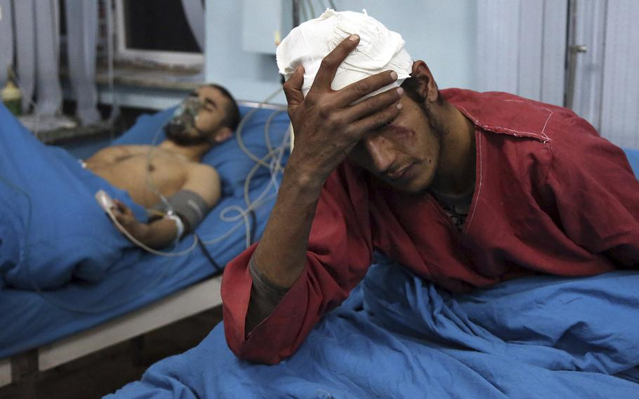 Injured men receive treatment at a hospital after a suicide bombing in Kabul, Afghanistan, Nov. 20, 2018.