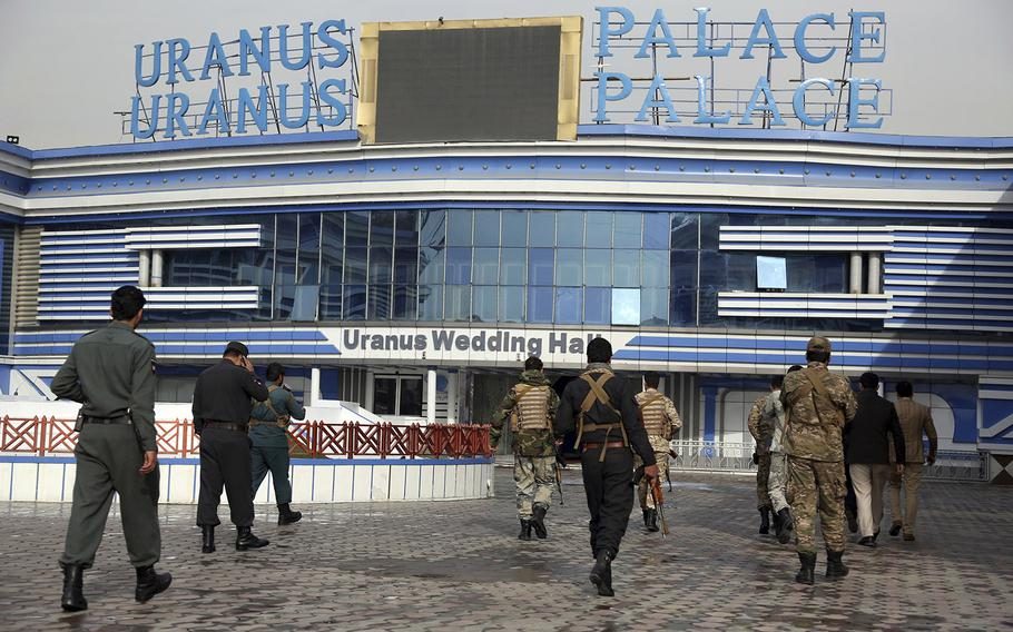 Afghan security personnel walk outside a wedding hall in Kabul, Afghanistan, Wednesday, Nov. 21, 2018, a day after a suicide attack.