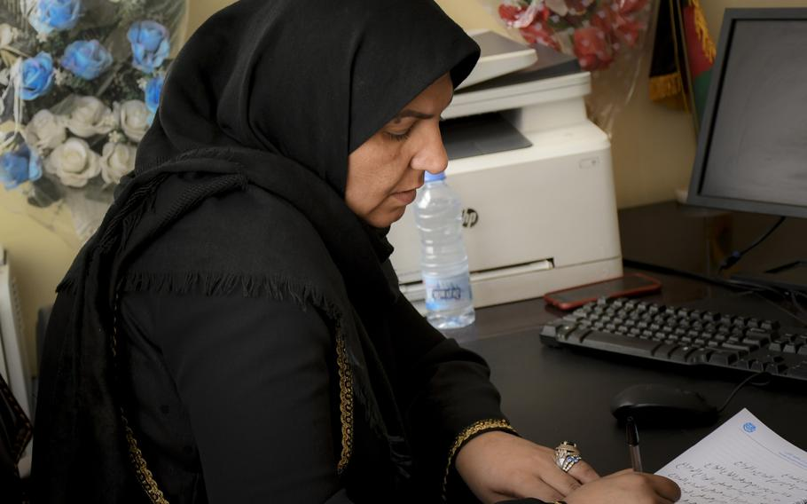 Na'ema Mawdadi, an Afghan police officer since 2007, writes out a poem Oct. 29, 2018 at the Herat municipal police headquarters. In the poem, which she wrote after last year's bombing of the German Embassy in Kabul, Mawdadi says goodbye to friends lost, and says goodbye to bad memories as well.
