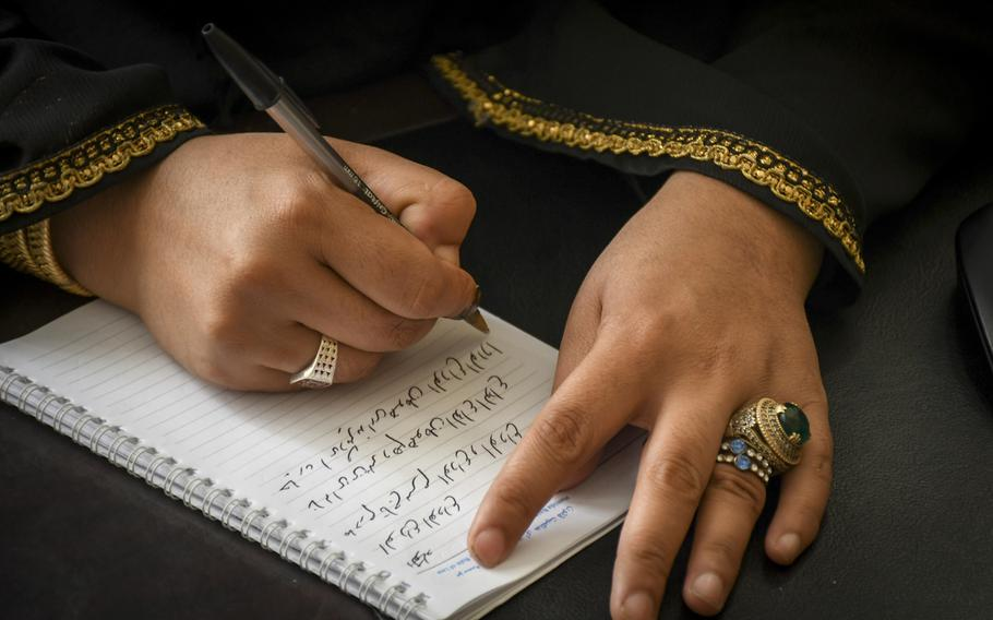 Na'ema Mawdadi, an Afghan police officer since 2007, writes a poem Oct. 29, 2018, at the Herat municipal police headquarters. In the poem, which she wrote after last year's bombing of the German Embassy in Kabul, Mawdadi says goodbye to friends lost, and says goodbye to bad memories as well.