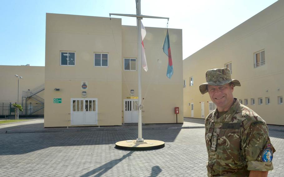 Lt. Guy Wadge, spokesman for U.K. Naval Support Facility Bahrain, poses in front of the installation's administration building.