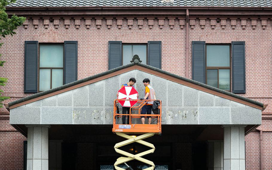 South Korean workers remove the signage from Eighth Army's former headquarters at Yongsan Garrison in Seoul, South Korea, July 10, 2017.