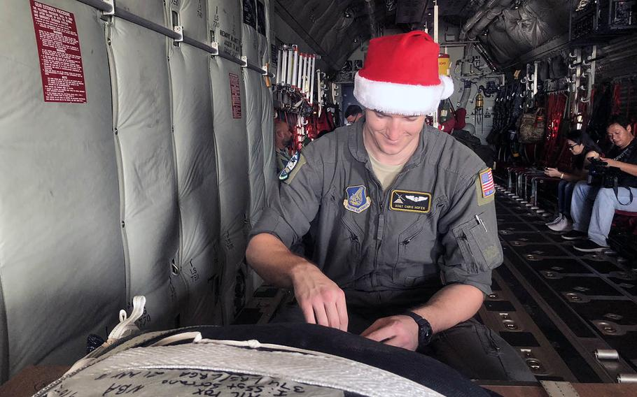 Staff Sgt. Chris Hofer, a loadmaster from Yokota Air Base, prepares a box of Operation Christmas Drop donations on board a C-130 Super Herc on Dec. 9, 2018.