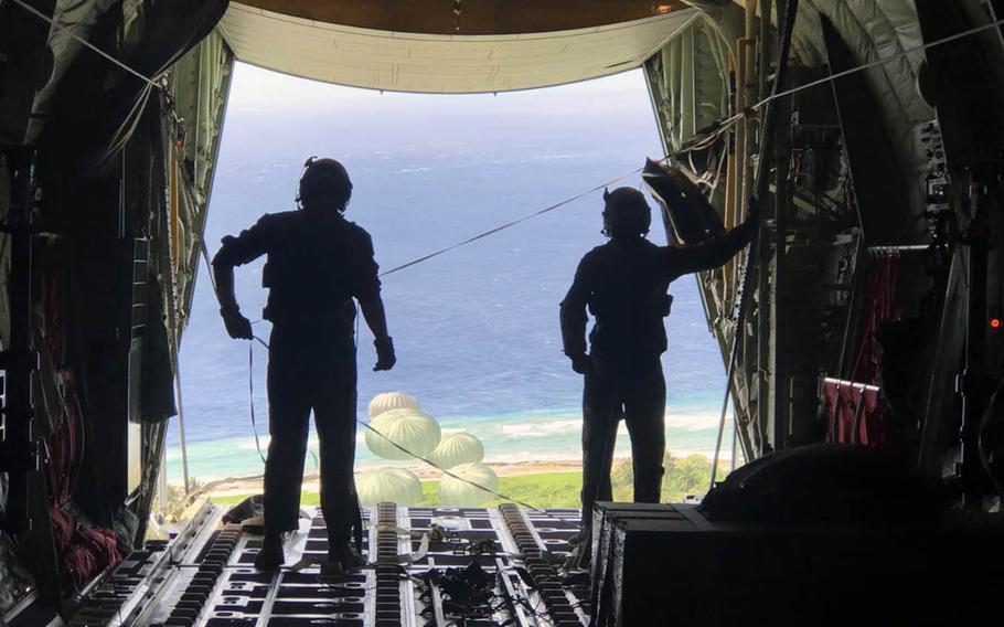 Staff Sgt. Chris Hofer and Senior Airman Walter Frank watch as parachutes open to carry Operation Christmas Drop donations to islanders below.