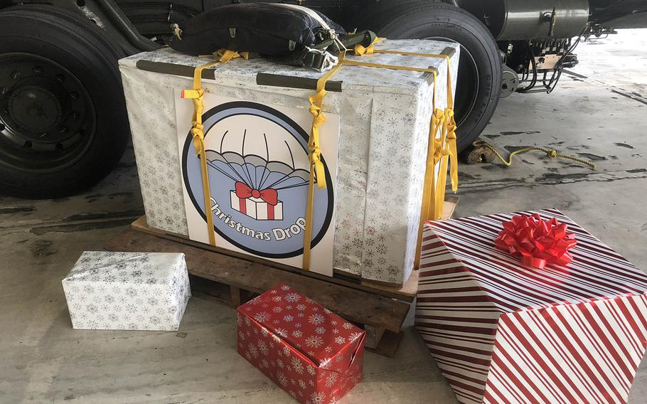 A box of Operation Christmas Drop donations was wrapped in Christmas paper for a special ceremony for servicemembers, volunteers and regional leaders.