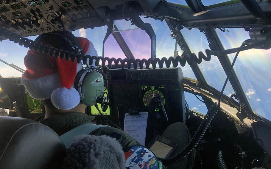 A C-130 pilot wears a Santa hat and an Operation Christmas Drop patch during a flight over the Northern Marianas Islands.