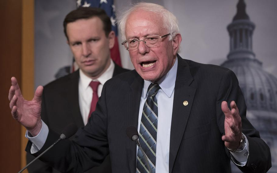 Sen. Bernie Sanders, I-Vt., speaks to reporters on Capitol Hill after the Senate passed a resolution he introduced that would pull assistance from the Saudi-led war in Yemen, Thursday, Dec. 13, 2018. Behind him is Sen. Chris Murphy, D-Conn.