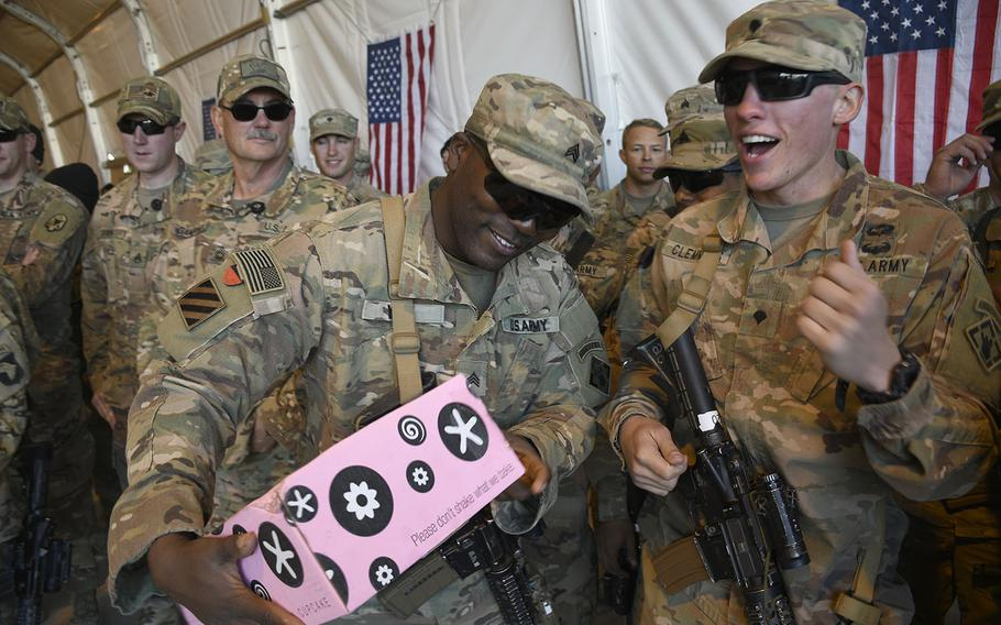 Soldiers of the 264th Engineer Clearance Company celebrate the arrival of artisanal cupcakes sent to them at the remote Camp Dahlke West in Afghanistan during a Christmas event with the USO on Monday, Dec. 24, 2018.
