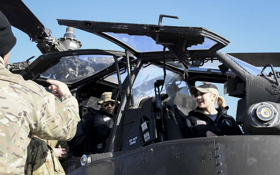 Country musician Kellie Pickler sits in the cockpit of an AH-64 Apache attack helicopter at a Christmas event with the USO on Monday, Dec. 24, 2018, at Camp Dahlke West in Afghanistan.