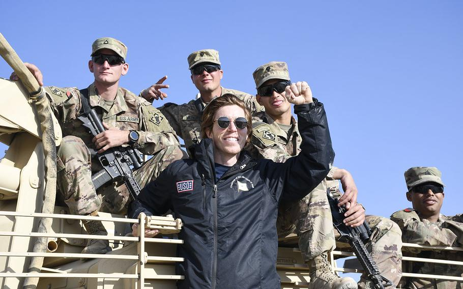 Snowboarder Shaun White poses with troops gathered at a Christmas event with the USO on Monday, Dec. 24, 2018, at Camp Dahlke West in Afghanistan.