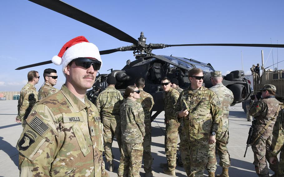 Spc. Adam Wells, 25, an armament soldier with the 4th Battalion (Attack Reconnaissance), 4th Aviation Regiment, watches as celebrities inspect his AH-64 Apache attack helicopter at a Christmas event with the USO on Monday, Dec. 24, 2018, at Camp Dahlke West in Afghanistan.