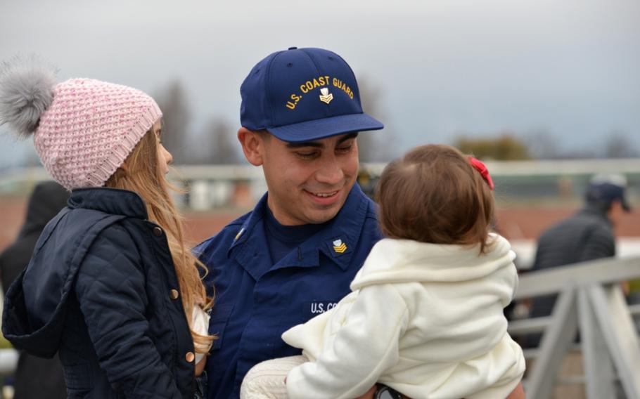 A Coast Guard Cutter Munro crewmember embraces his children after the cutter returned home to Alameda, Calif., Dec. 24, 2018.