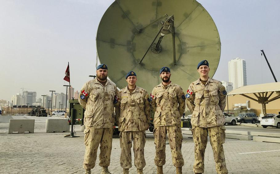 Combined Task Force 150 members Master Cpl. David Jackson, Cpl. Robert Pottage, Cpl. Marc Delaney and Cpl. Timothy Schultz stand in front of a satellite on Naval Support Activity Bahrain, January 23, 2019.  The team made up of 30 Canadians and seven Australians work with 10 other Canadians running the Unclassified Remote-Sensing Situational Awareness satellite system. URSA monitors maritime traffic in the Persian Gulf and the historic narcotics ''smack track'' in the Arabian Sea and Indian Ocean.
