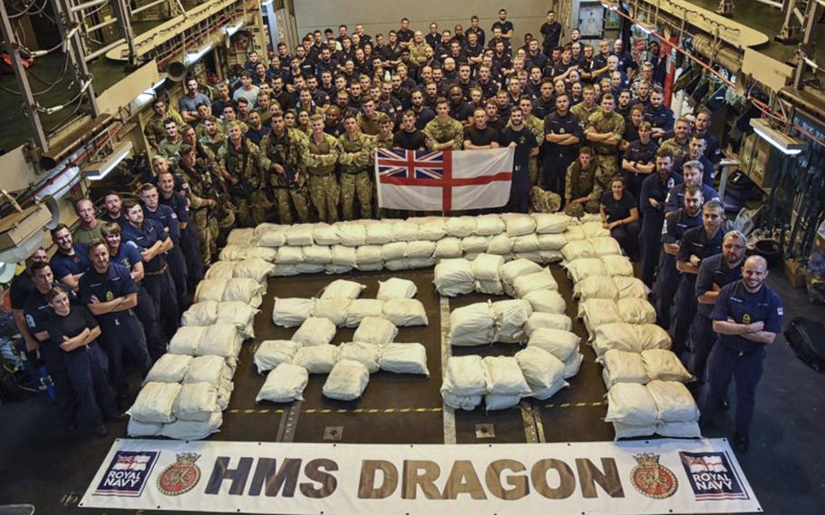 The crew of the British destroyer HMS Dragon poses for a photo with a drug haul.