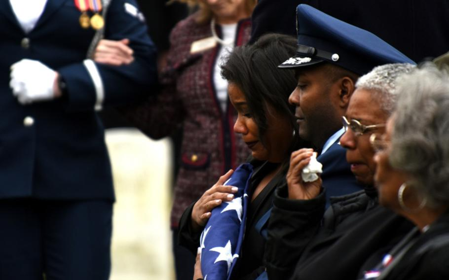 Tenecia Harris, daughter of Marcelite Harris, holds the American flag during her mother's funeral at Arlington National Cemetery on Feb. 7, 2019.