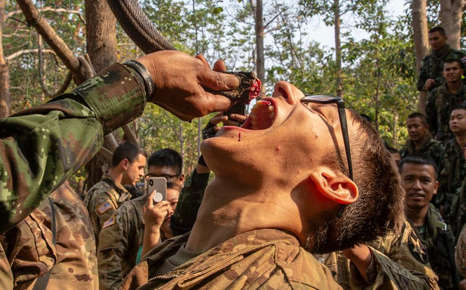 Royal Thai Armed Forces Master Sgt. 1st Class Saengchai Seeuthai pours cobra blood into the mouth of a U.S. soldier of the 20th Infantry Regiment during exercise Cobra Gold 19 at Phitsanulok, Thailand, on Feb. 13, 2019.