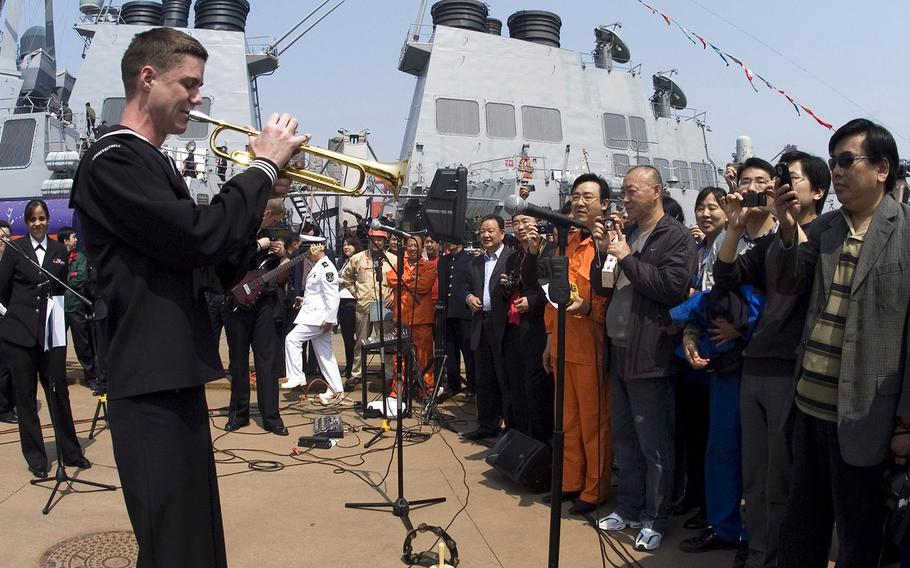 In a 2009 file photo, Petty Officer 2nd Class Collin Reichow plays a trumpet solo on the pier at Qingdao for Chinese citizens waiting to tour the guided-missile destroyer USS Fitzgerald during the International Fleet Review celebrating the 60th anniversary of the founding of the People's Liberation Army navy. The Pentagon says the U.S. won't be taking part in the 70th anniversary events this year.