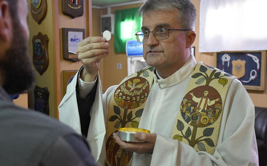 Father Giovanni Scalese, chaplain at the Italian Embassy in Kabul, distributes communion at a Catholic Easter mass at NATO's Resolute Support headquarters in the Afghan capital on April 21, 2019.