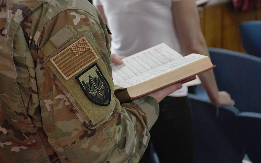An American servicemember sings from a hymn book during an Easter service at NATO's Resolute Support headquarters in Kabul, Afghanistan, on Sunday, April 21, 2019.