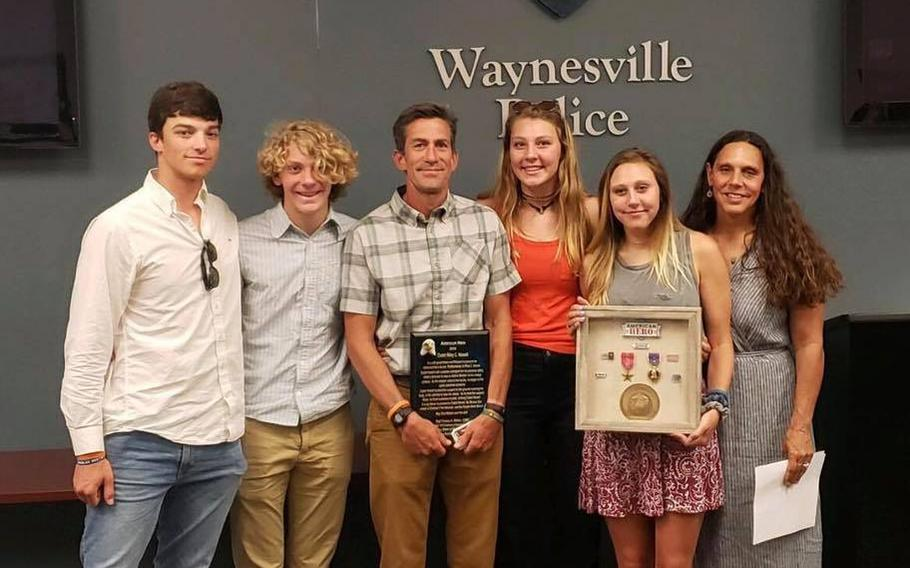 """The parents and siblings of Riley Howell hold a plaque and framed medals that were presented from the Waynesville, N.C., Police Department and Haywood County Sheriff Greg Christopher. The medals were donated by Marine Corps veteran Thomas """"Stormy"""" Matteo."""