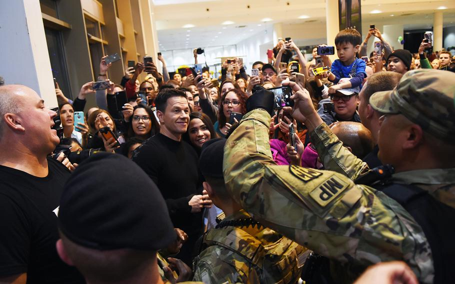 Actor Mark Wahlberg greets the crowd and poses for photos inside the food court at Ramstein Air Base, Germany, on Dec. 15, 2019. Mark Wahlberg and his brothers, Paul, a chef, and Donnie, an actor, founded the restaurant in 2011. The Ramstein location will open early next year and will be the first on a U.S. military base.