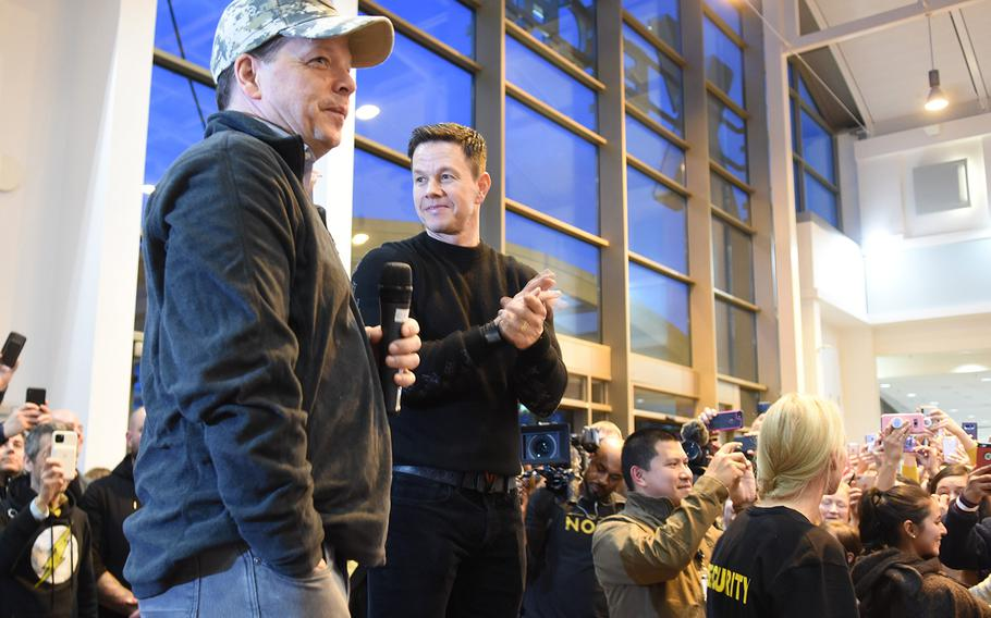 From left, Paul Wahlberg, a chef, and his brother, actor Mark Wahlberg, stand in front of a large crowd inside the food court at Ramstein Air Base, Germany, where a new Wahlburgers is scheduled to open in early January. The brothers visited the base Sunday, Dec. 15, 2019, to meet service members and their families and to talk about the restaurant.
