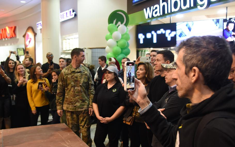 Actor Mark Wahlberg and his brother, Paul, a chef, stand in the middle of a large crowd in front of their fast-casual burger joint, Wahlburgers, set to open in early January at Ramstein Air Base, Germany. The brothers visited with service members on Sunday, Dec. 15, 2019.